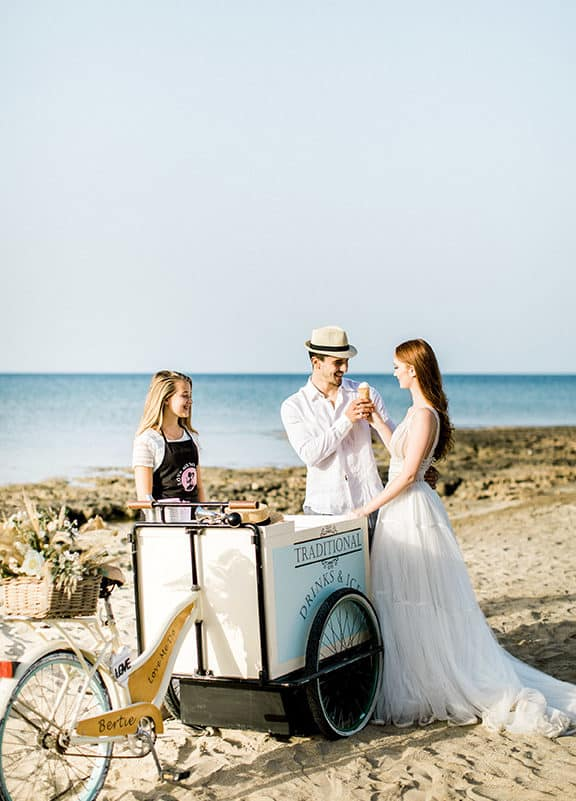 bride and groom have an ice cream at the beach