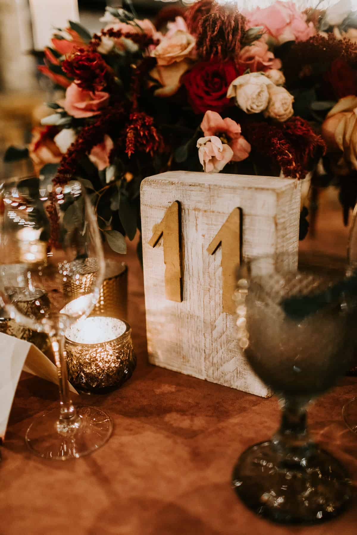wedding wooden table numbers and red flowers