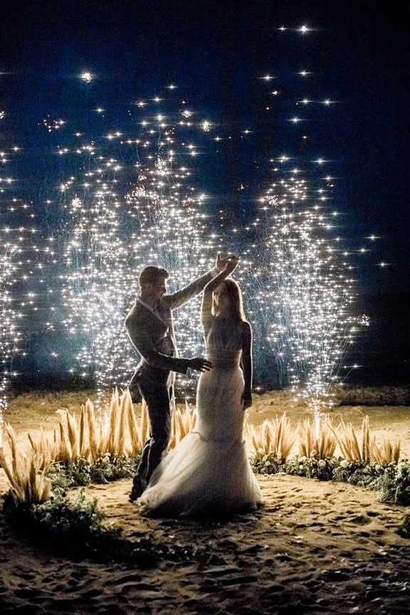 wedding photography bride and groom dancing at the beach with fireworks
