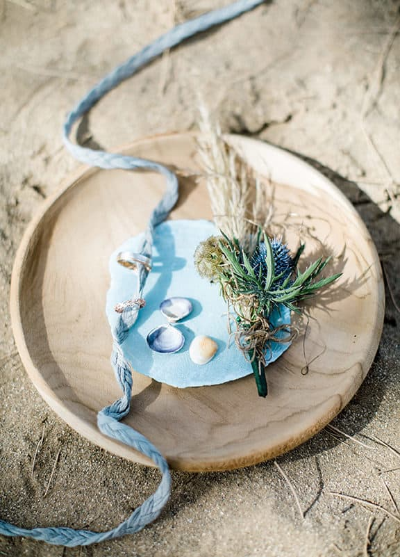 wedding rings in a wooden plate with blue ribbon
