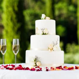 Modern 3-tier white wedding cake with flora decoration made by Ariston Confectionery, and two glasses of champagne.