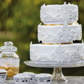 A white, 3-level wedding cake and cupcakes made with love by Aroma Vanilias in Cyprus.