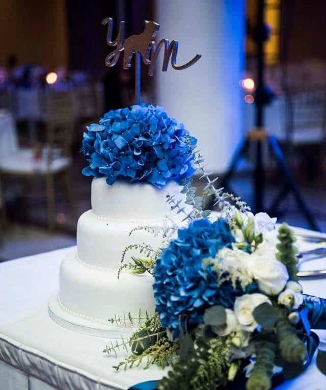 wedding cake decorate with blue hydrangeas and the bridal bouquet