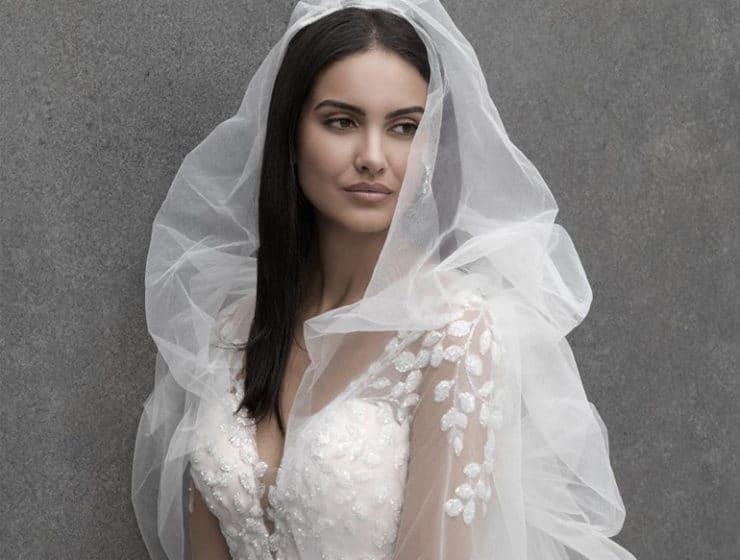A wedding dress with a light lace shawl, by Carla Bridal.