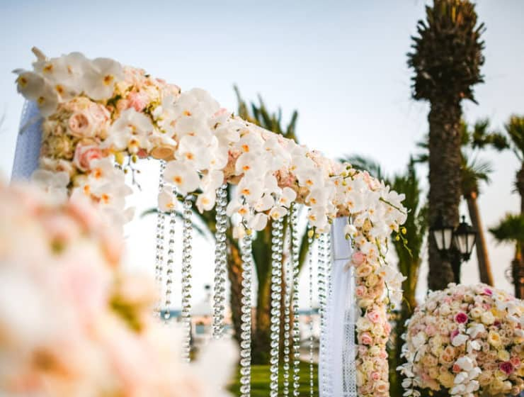 Wedding arch decorated with glass beads and white flowers, made by Cosmea Gardens in Cyprus.