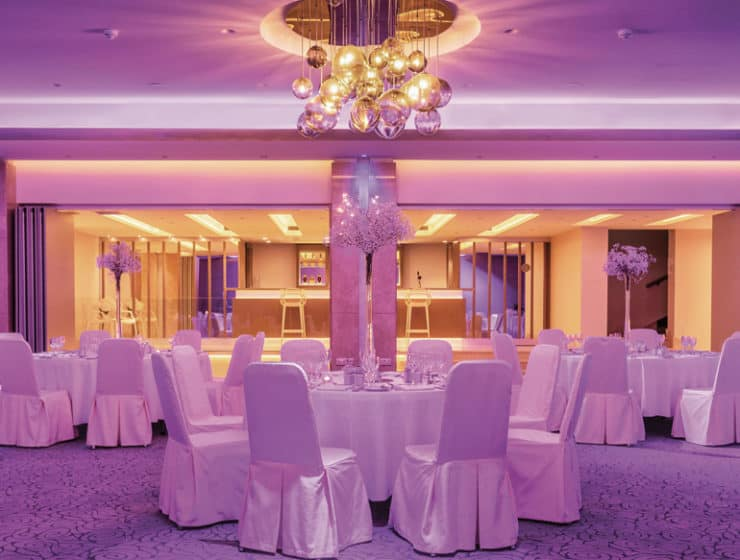 White wedding tables with purple lighting, for a reception at Crowne Plaza Limassol Hotel.