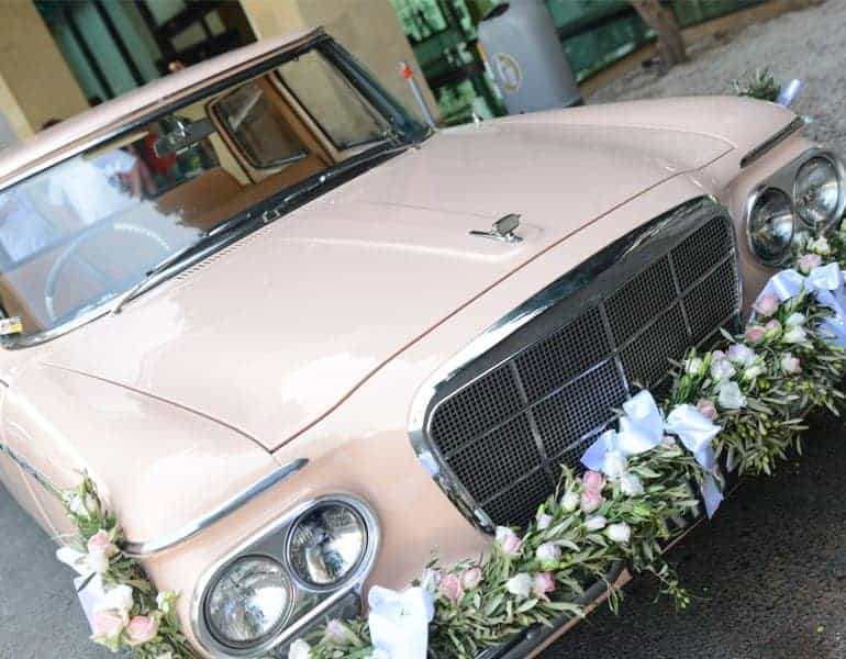 Vintage white wedding car decorated with flowers, by Cyprus Motor Museum.