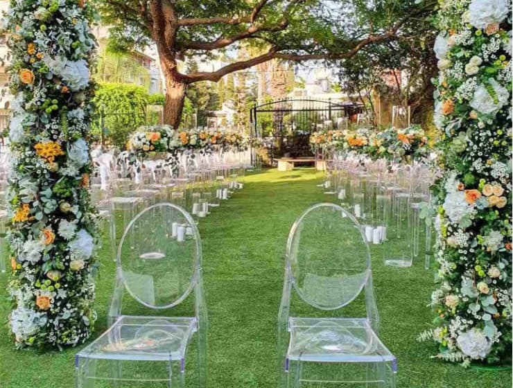Wedding ceremony flower decorations in a garden, by Design by Sakis.