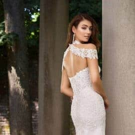 An open back wedding dress and long earrings, design by Ensemble Bridal Boutique.