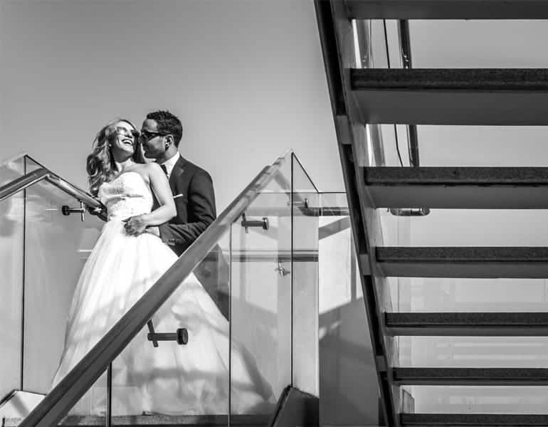 A couple in their wedding clothes at a photoshoot on a staircase; shooting and editing by Foto Larko in Cyprus.