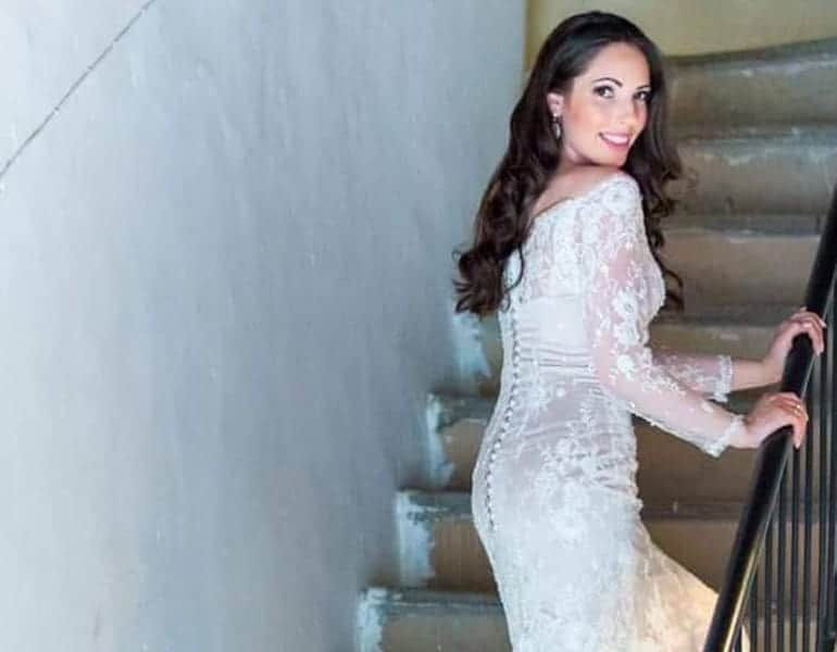 A tight, strapless wedding dress worn by a model climbing the stairs, designed by Georgelen in Cyprus.