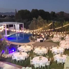 An overhead view of a wedding reception dinner and with hanging lights, at the pool of Ktima Elaiokipoi in Nicosia, Cyprus.