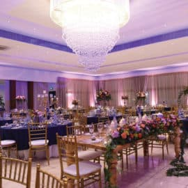 A glamorous wedding reception setup, with flowers and a bright chandelier, at Ktima Kousioumi.