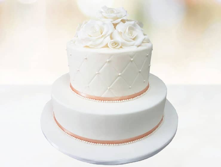 Classic white wedding cake with confectionery roses, made by La Patisserie Panayiotis.