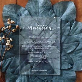 Plexiglass wedding invitation in a blue leaf background, produced by Le Beau by Print Xpress.