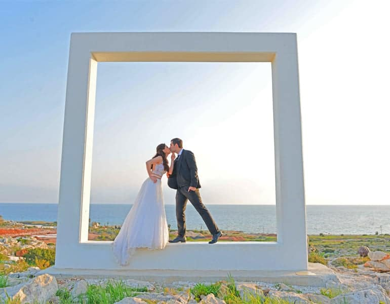 A couple in a white square statue by the sea, during a wedding photoshoot by My Sunshine Photography.