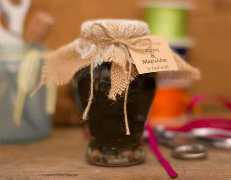 A jar of traditional cypriot sweets by Niki's Traditional Sweets, as a wedding favour gift, decorated with the couple's names and wedding date.
