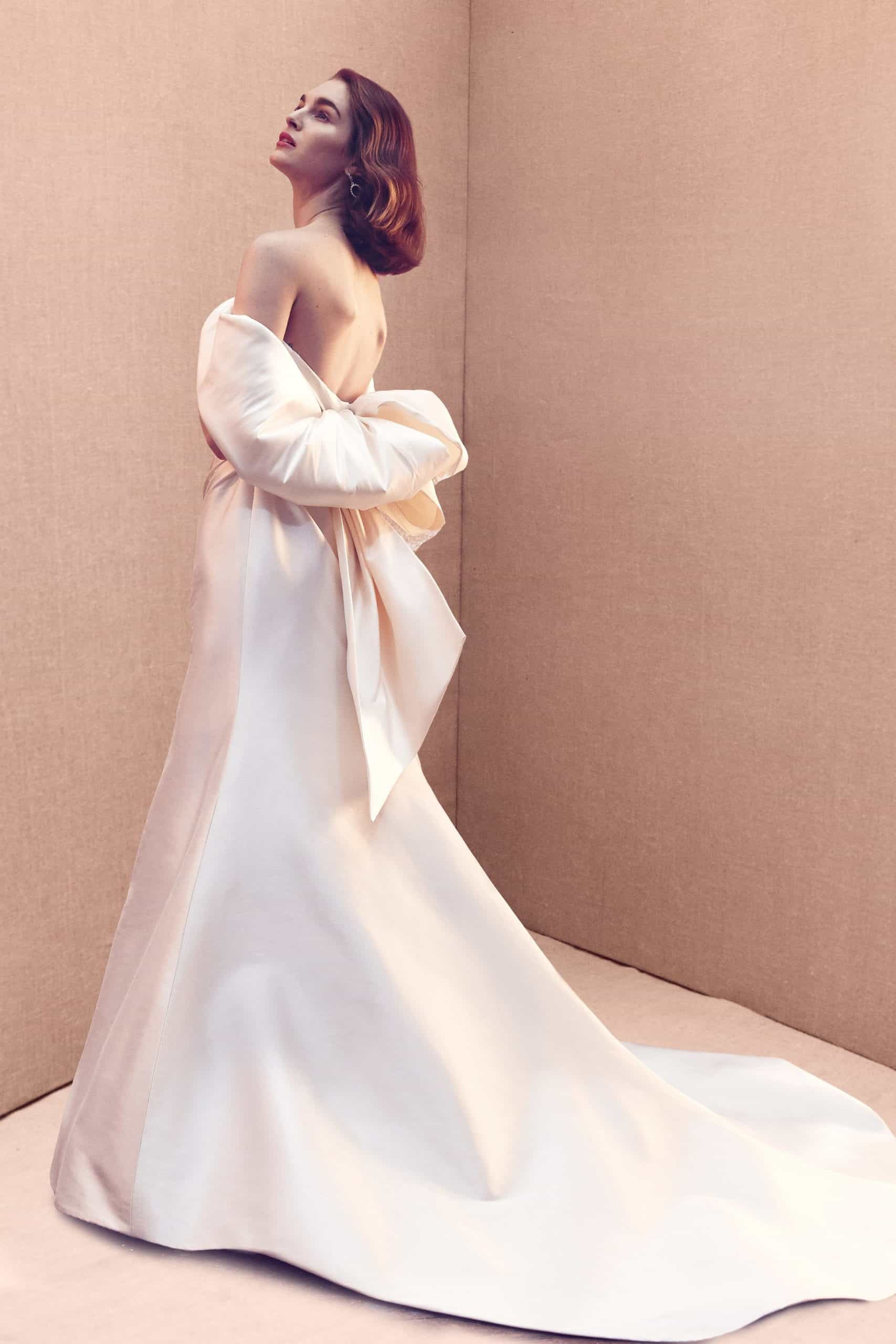 a stain wedding dress with a tail and back bow by Oscar de la Renta