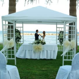 A white gazebo and wedding ceremony chairs at the beach, an option offered by Palm Beach Hotel at Larnaka.