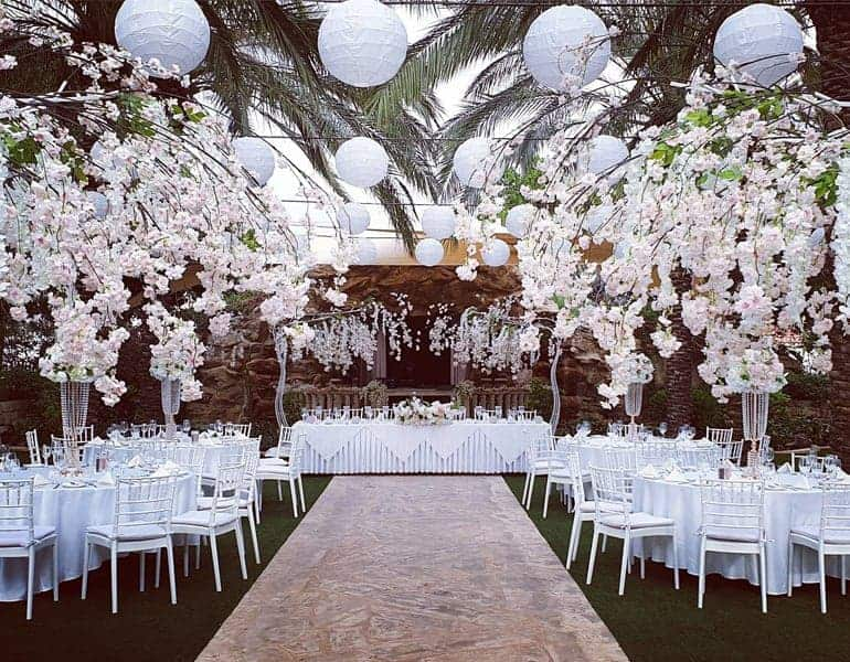 White flowers and hanging spheres decorating a wedding reception dinner, made by Paper Flowers Cyprus.