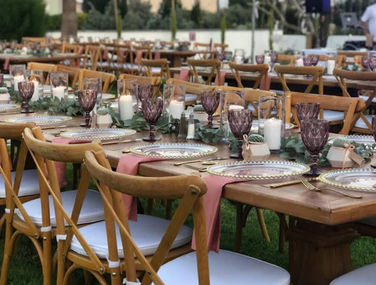 Chairs and tableware for a wedding reception, decorated by Party Guide Wedding Rentals.