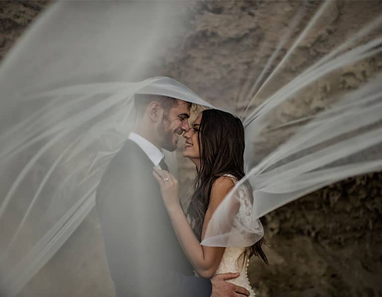 A couple in intimate moments under white lace, during a wedding photoshoot by Photo Bella Photography.