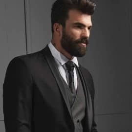 A black suit with a light blue shirt and a black tie worn by a bearded model, by Posh Boutique Cyprus.