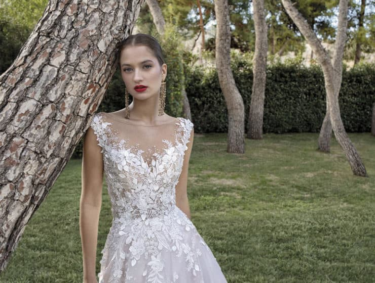 Floral wedding dress with long, golden earrings, made by Renee Bridal in Cyprus.