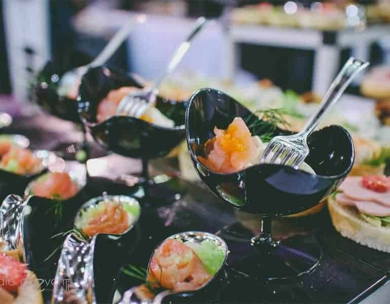 Appetisers with caviar in stylish black bowls at a wedding dinner, produced by Sans Frontieres Catering.