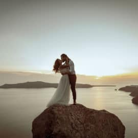 A couple in wedding clothes standing on a rock with a beautiful background of the sea, by Savvas Demetriou Photography.