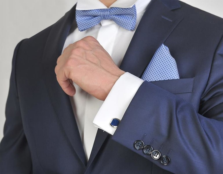 A designer groom suit with a bowtie, sold by Sofianos.