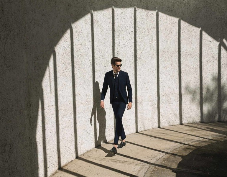 A model wearing a stylish blue suit and sunglasses, by Status Groom Suits inn Cyprus.