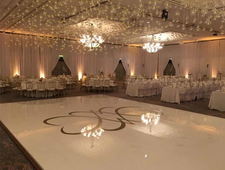 White dance floor and chandelier lights, designed by cypriot comparny S.Y. Stage wedding rentals.