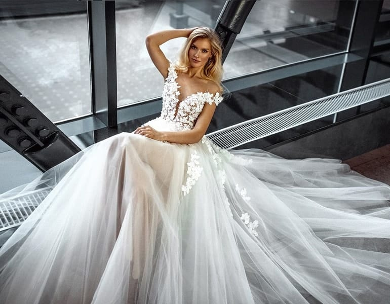 A blonde model in a lace, strapless wedding dress, by Versal Wedding Gallery in Cyprus.