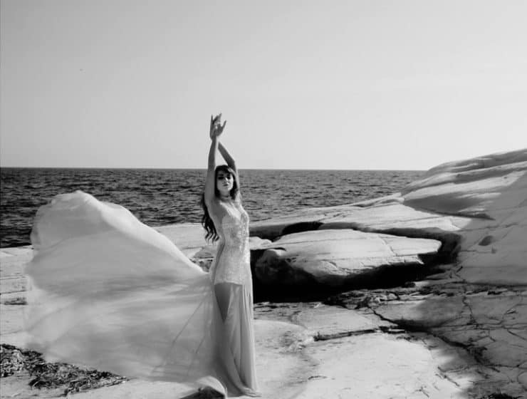 Wedding dress with an exquisite tail worn by a model at a photoshoot at the beach, design by Victoria Sarri Atelier.
