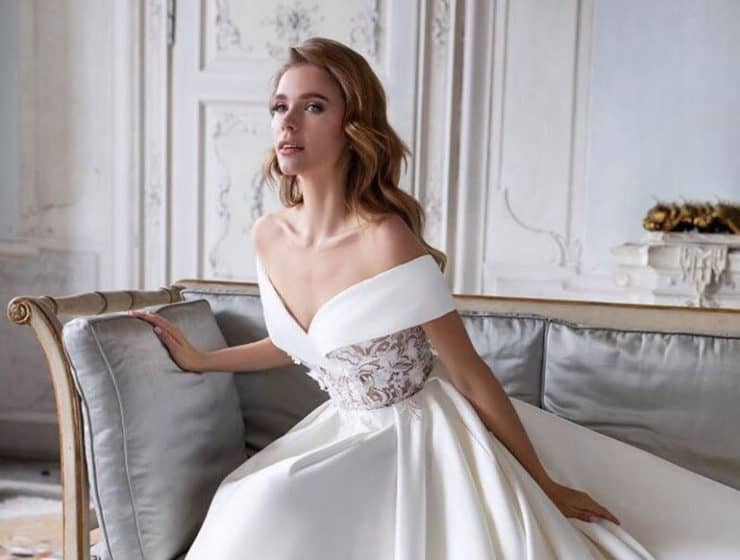 Model wearing a strapless wedding dress sitting on a fashionable couch, designed by Vision Collection in Cyprus.