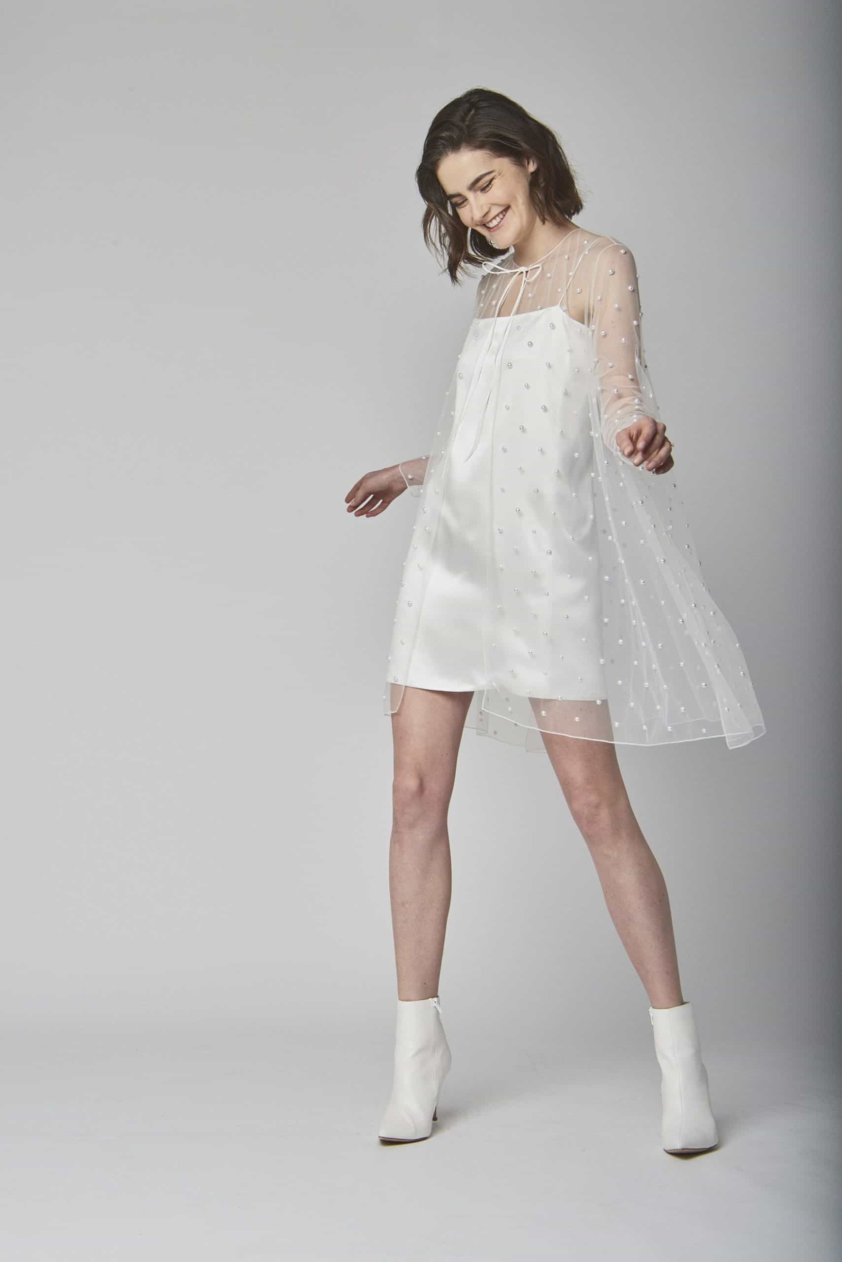 a short wedding dress with a tulle cape with pearls by Alexandra Grecco