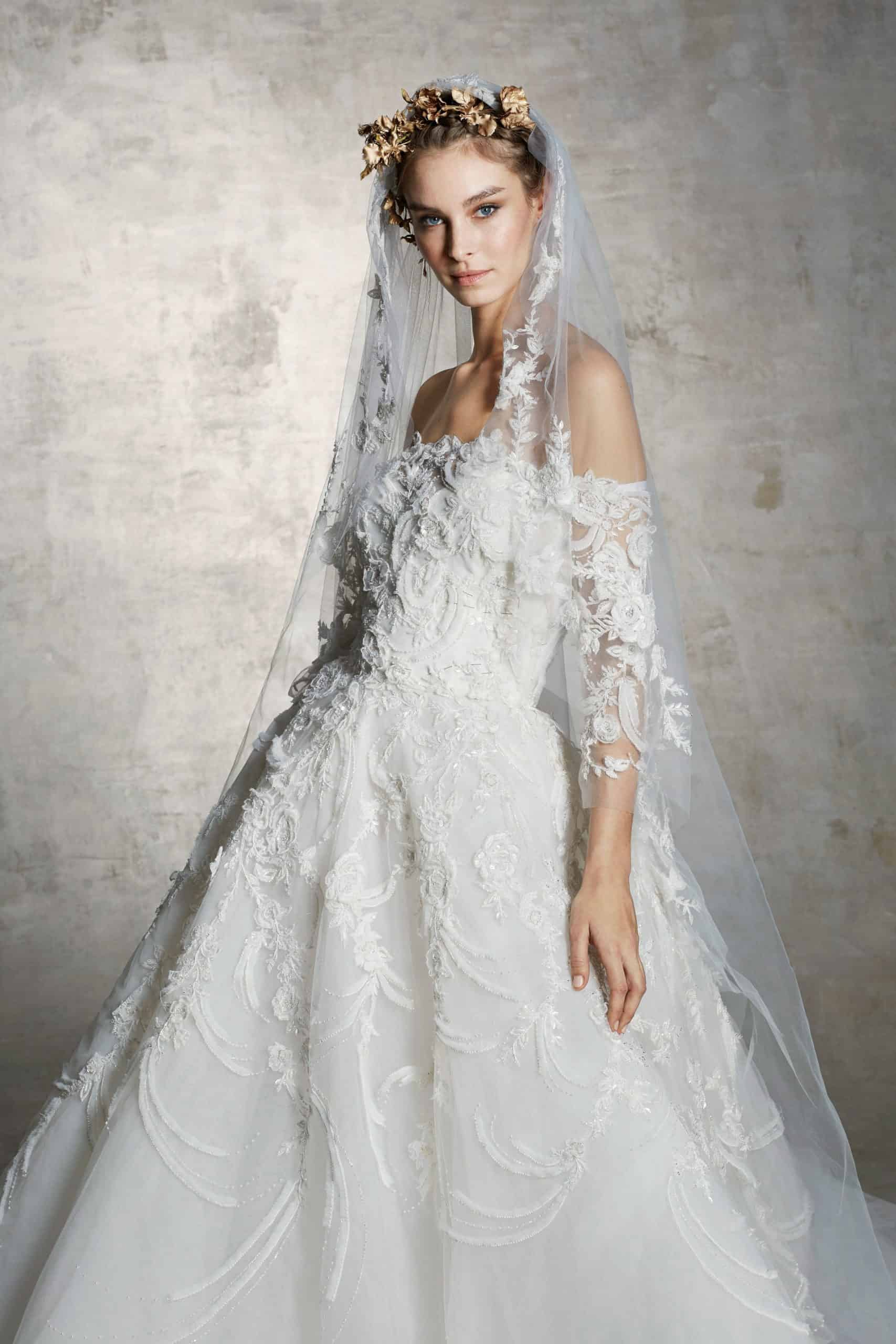 heavy lace wedding dress with a veil by Marchesa