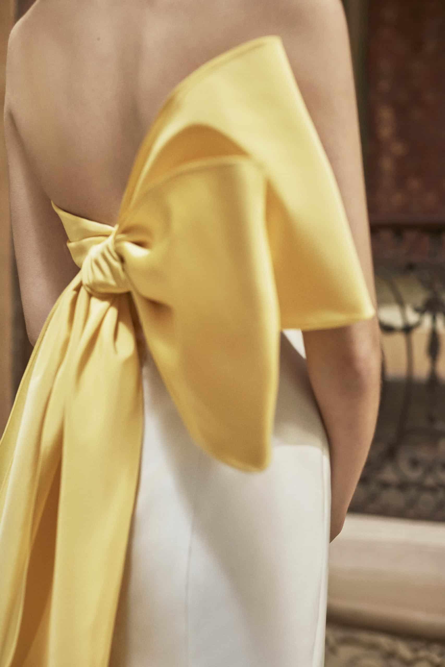 wedding dress with a huge yellow silk bow around the waist by Carolina Herrera
