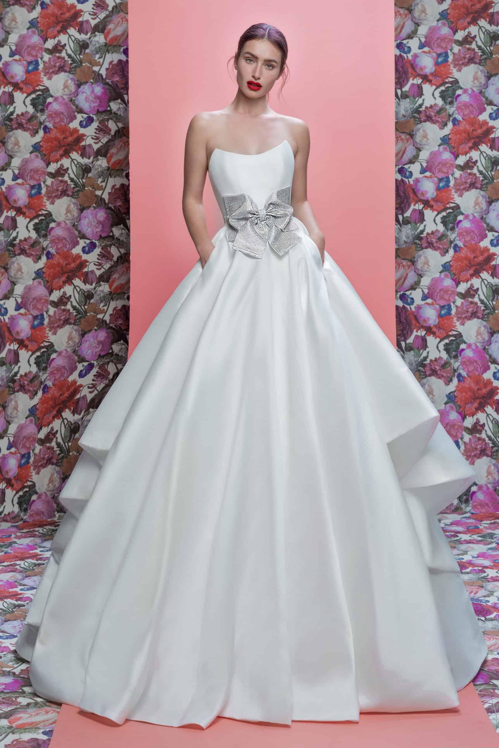 a princess style wedding dress with a silver bow around the waist by Galia Lahav