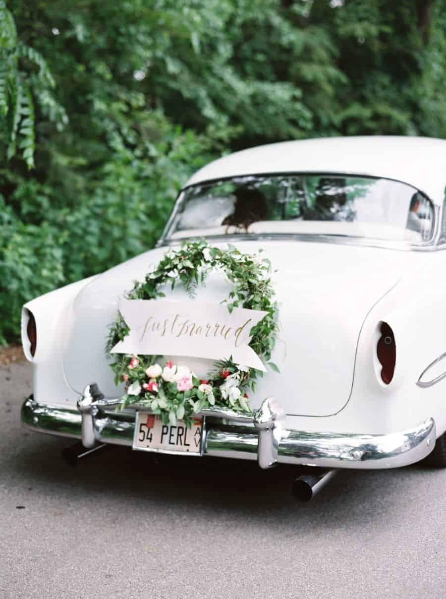 wedding car decoration with floral wreath just married