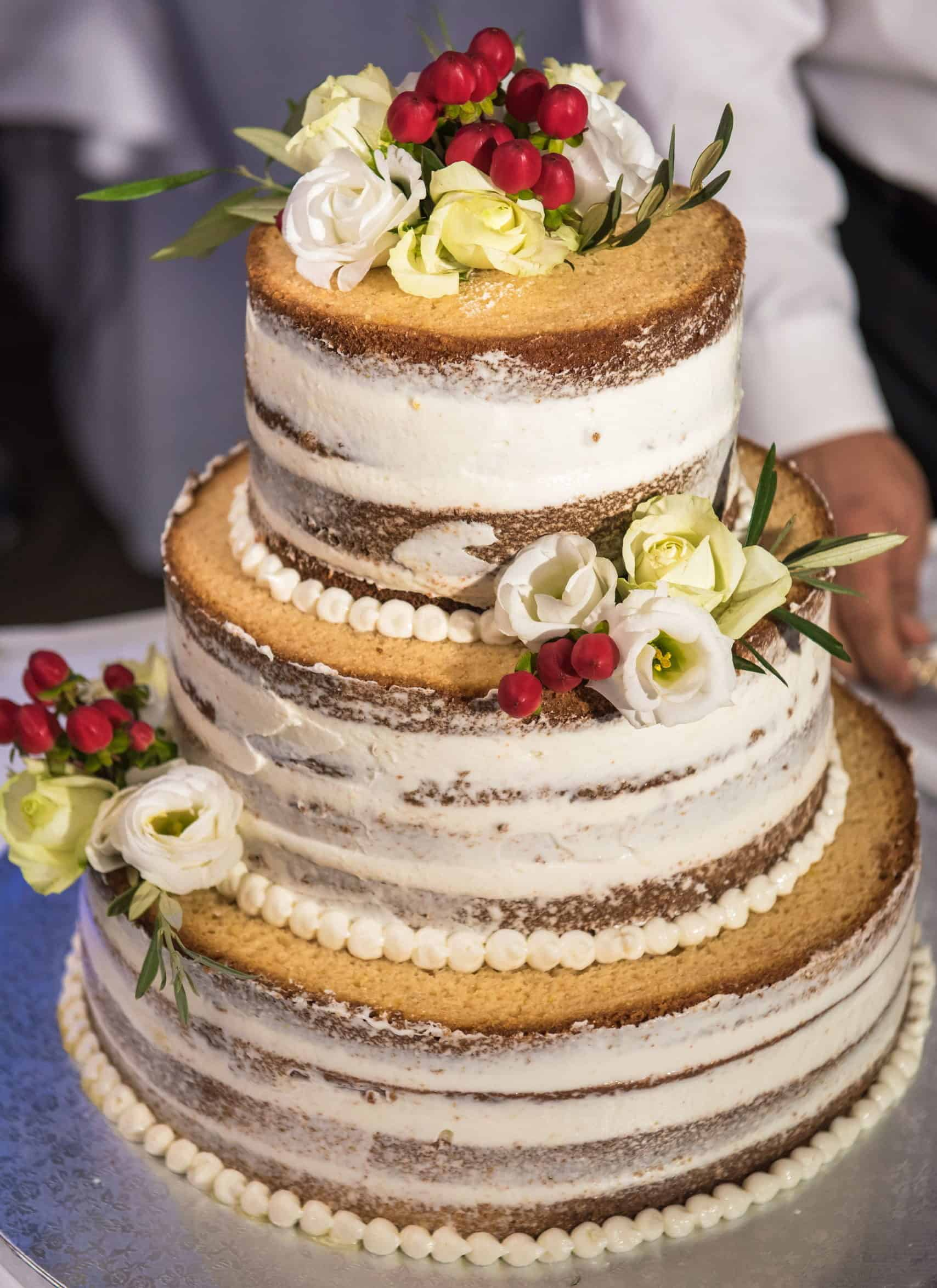 naked wedding cake with flowers and berries