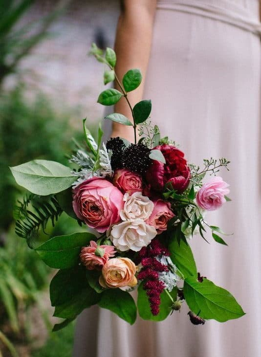 wedding bouquet with peony in pink and red shades, framed with greenery