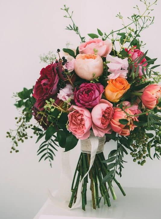 wedding bouquet with orange and pink roses and pink peony
