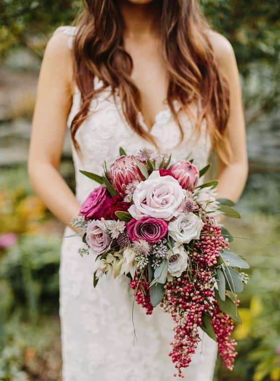 γαμήλια ανθοδέσμη με άνθη και μούρα σε ροζ και κόκκινες αποχρώσεις
