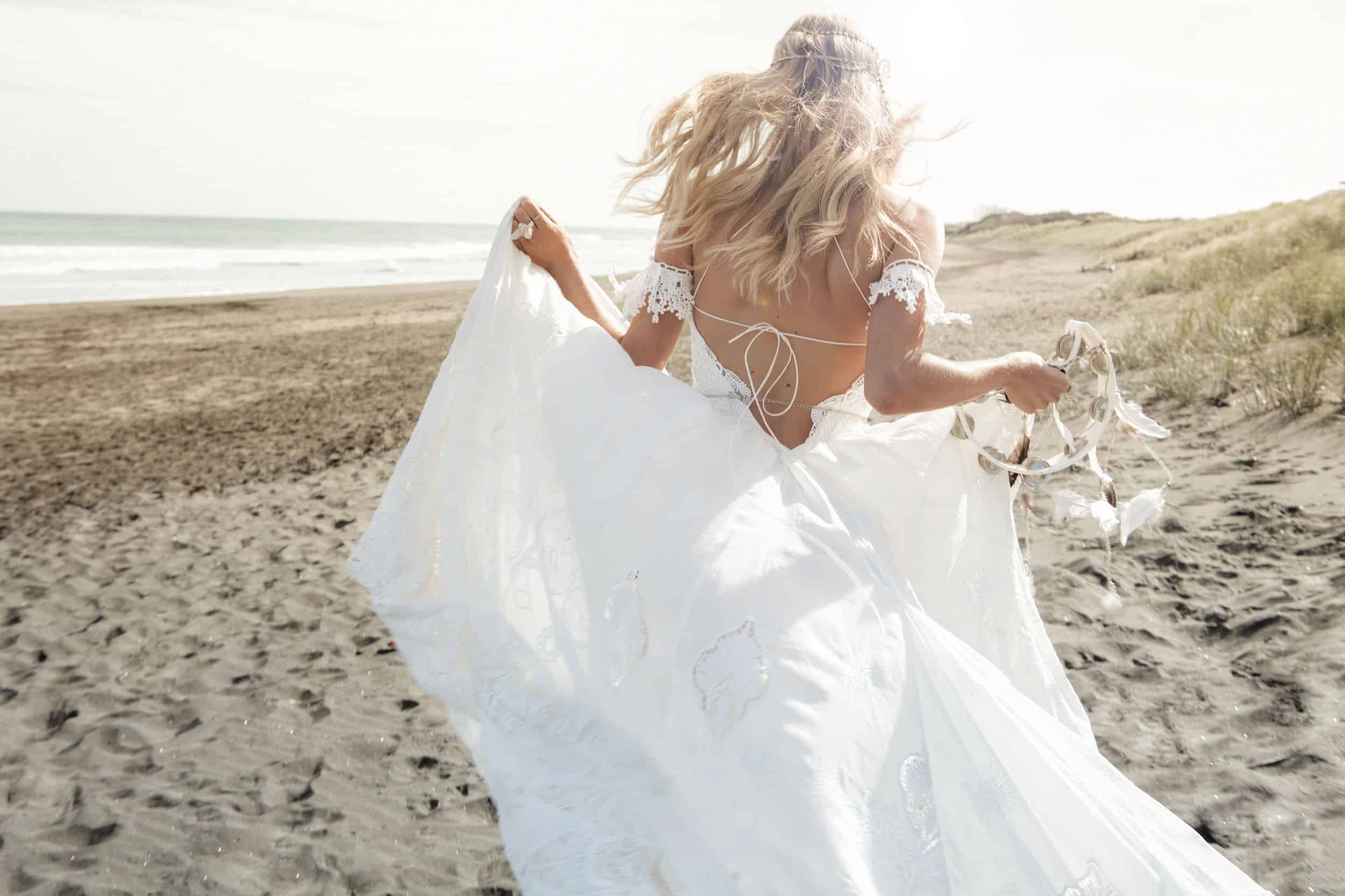 bride at the beach with a wedding dress with back side details