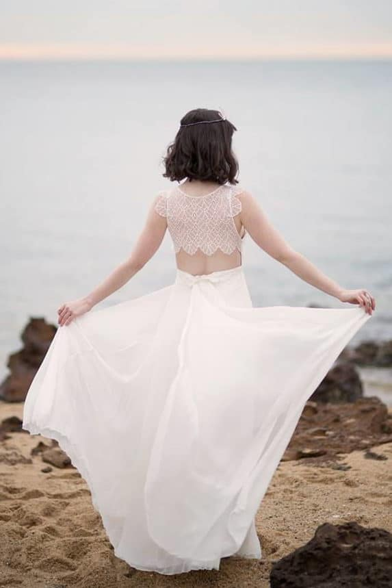 bride at the beach with a girly wedding dress. The back is partly covered by an ornate bodice