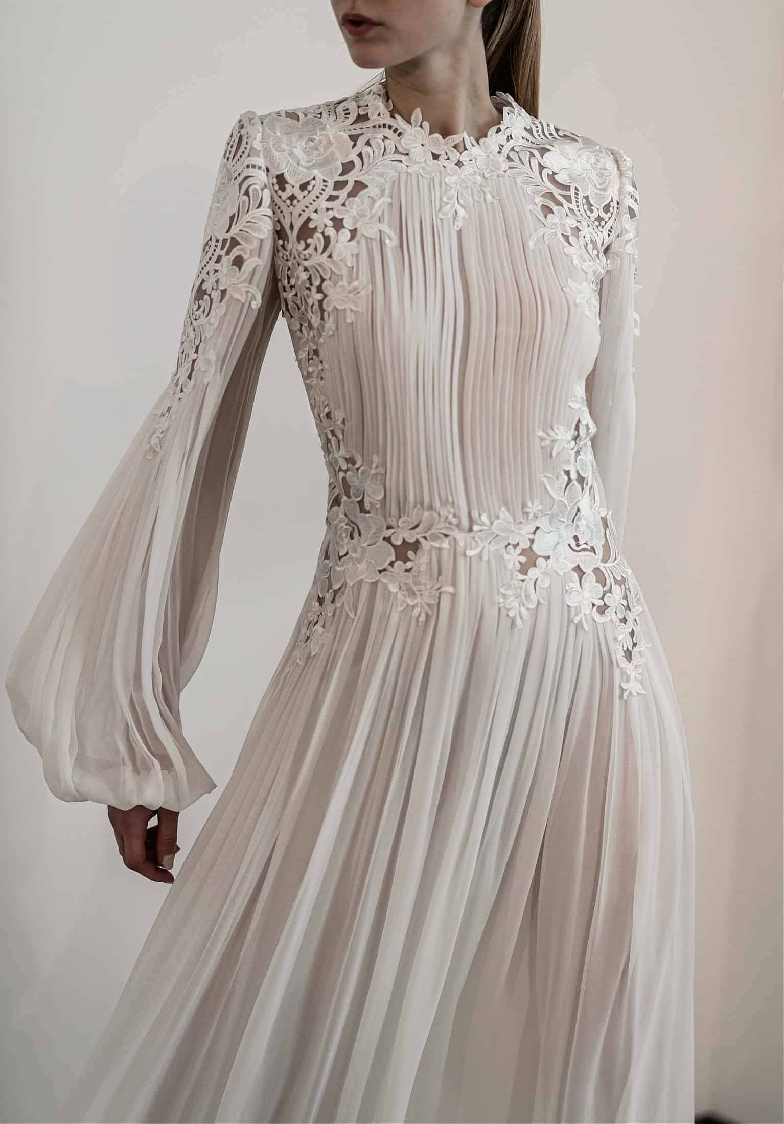 a wedding dress by Costarellos Bridal House with pleated base and long sleeves with lace details