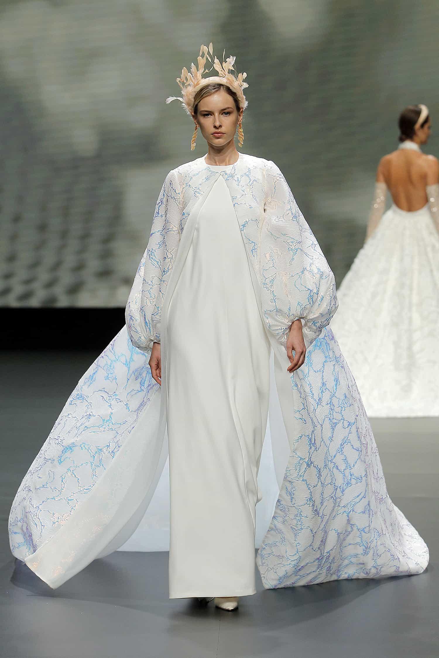a wedding dress with cape by Jesus Peiro