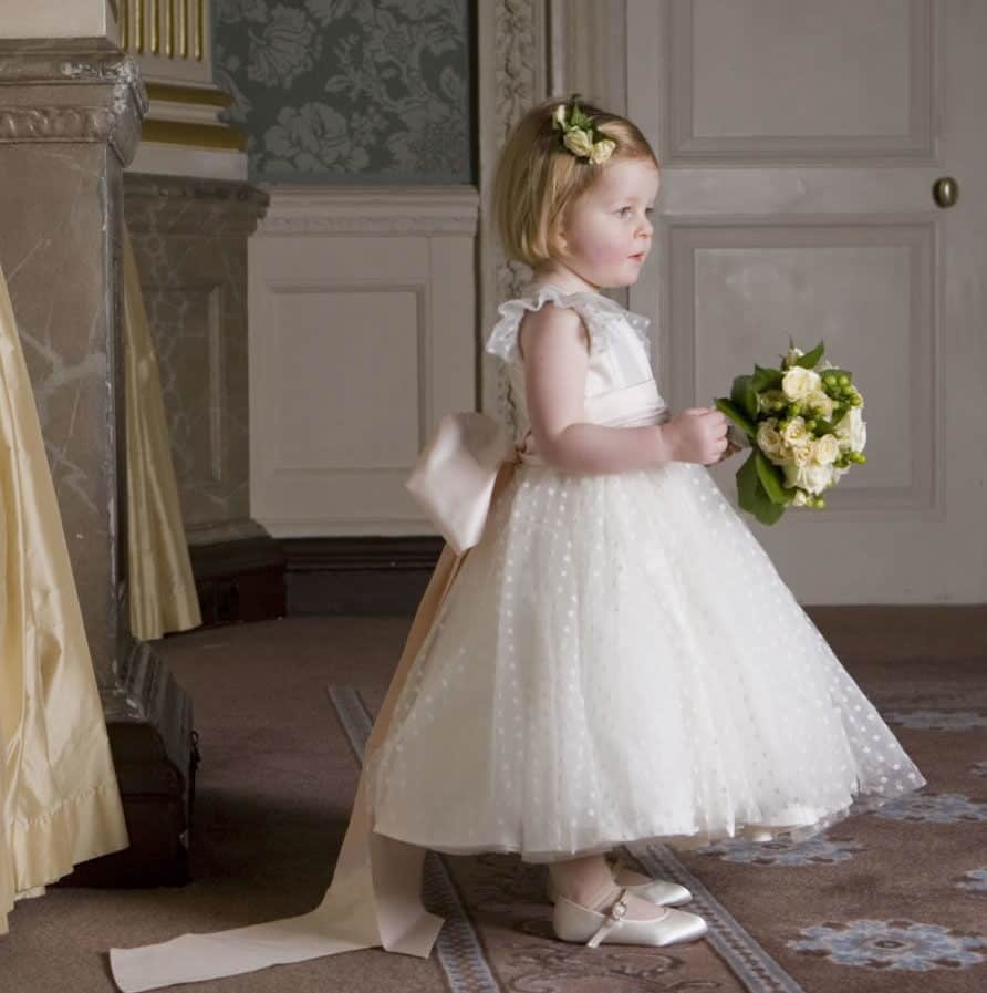 flower girl with classic royal style dress with a pink ribbon by Nicki Macfarlane